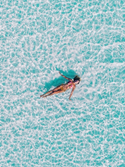 Woman floating in a clear blue sea
